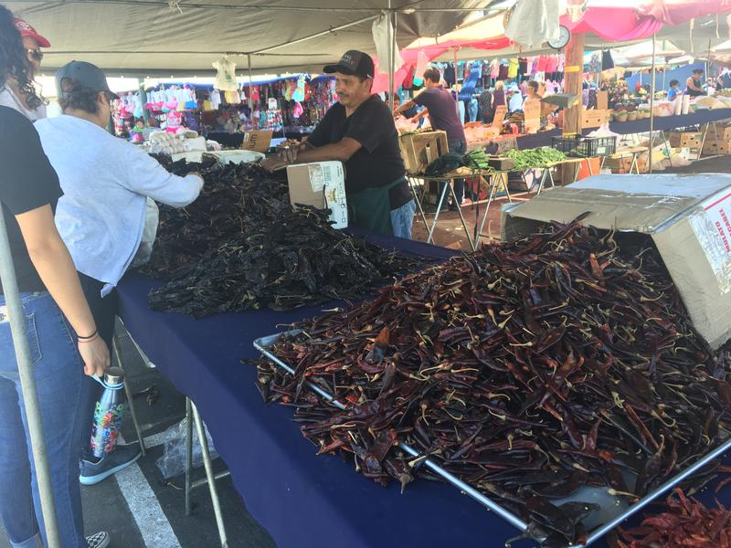 Jose Robles sells chilies to cutomers at his stand at the Cherry Avenue Auction in Fresno County.