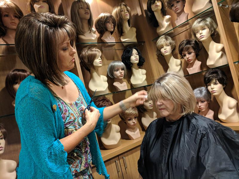 Lemonade Locks wig boutique owner Kelly Giblin fits a hairpiece onto realtor Brenda Blanton, who suffered from hair loss associated with the valley fever medication fluconazole.