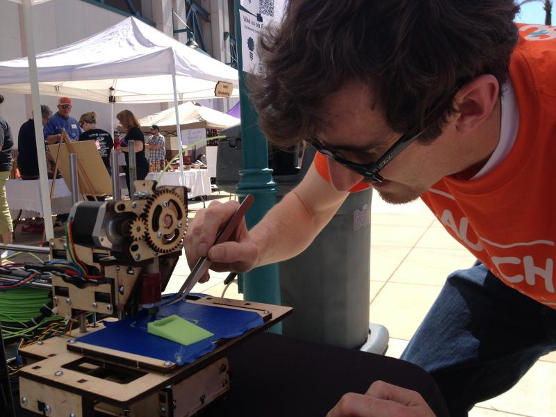 Chris McCoy, with the depart of mechanical engineering at UC Berkeley, tinkered with a 3D printer at the event.