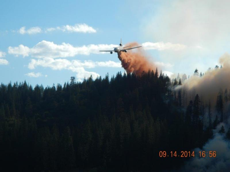 A DC-10 air tanker drops fire retardent on a forest ridge near the shore of Bass Lake.