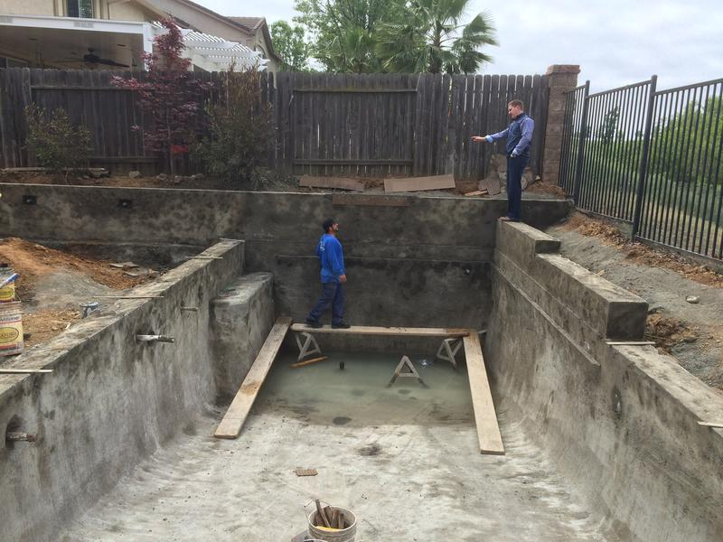 aron Gurley of Premier Pools and Spas discusses the pool installation with one of his workers.