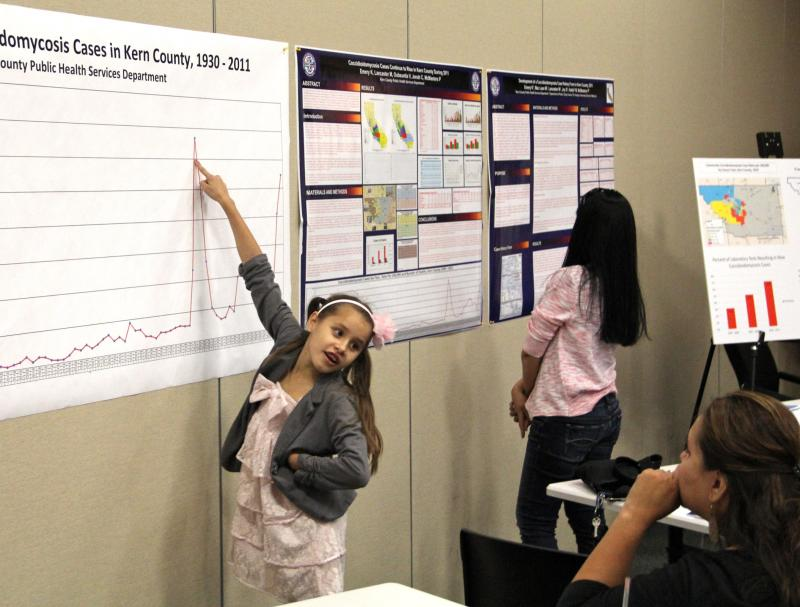 7-year-old Emily Gorospe points at a chart tracking the increase in reported cases of valley fever in Kern County from 1930 to 2011.