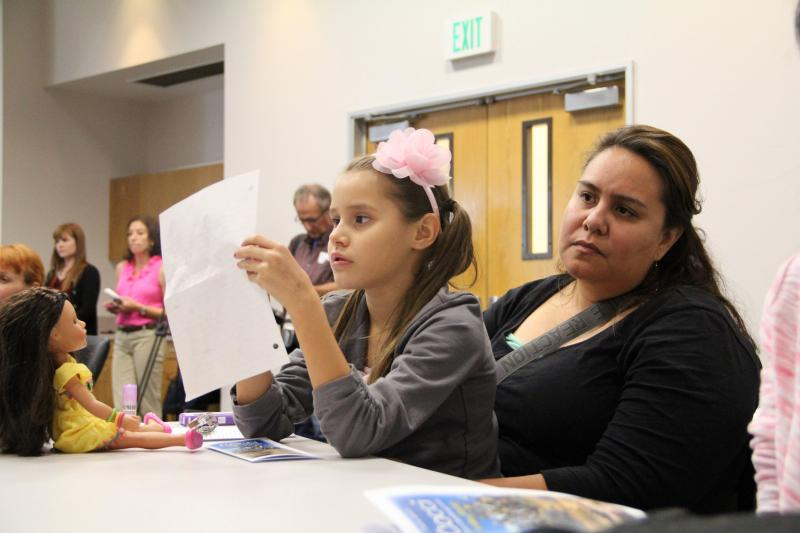 7-year-old Emily Gorospe and her mother Valerie Gorospe listen to panelists discuss the valley fever epidemic currently facing Kern County.
