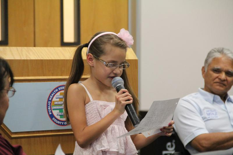 7-year-old Emily Gorospe reads from a handwritten note describing how valley fever has changed her life, at a town hall event in Bakersfield.