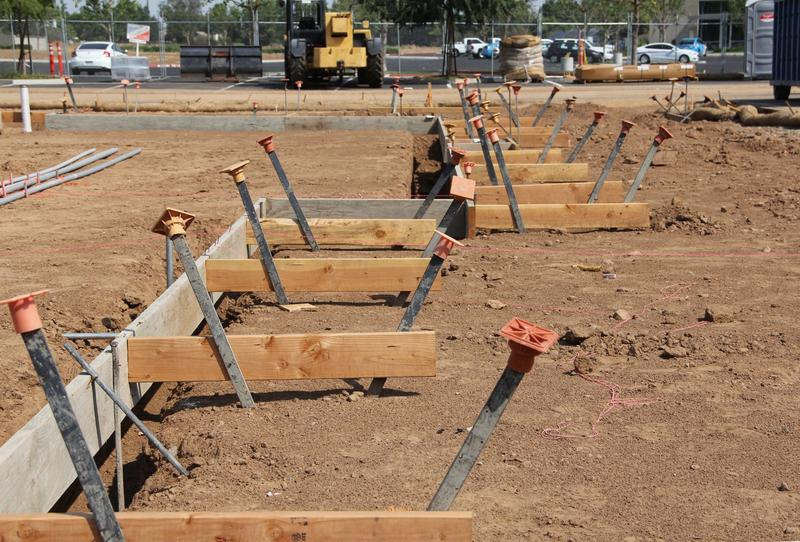 Boards and metal stakes are in place to hold steel rebar and concrete that will become the foundation for the new building