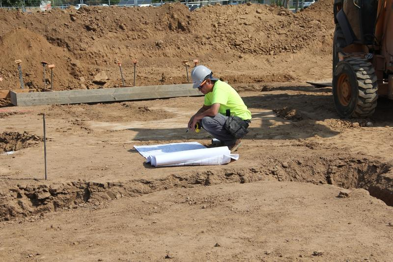 A worker studies plans for the project at the job site.