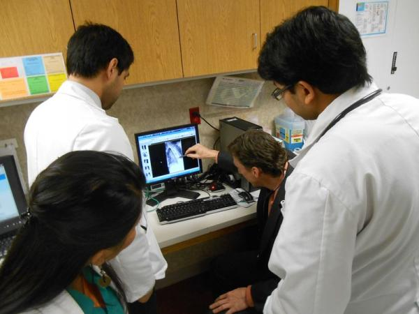 Dr. Peter Broderick examines a patient's X-ray as three future doctors look on.