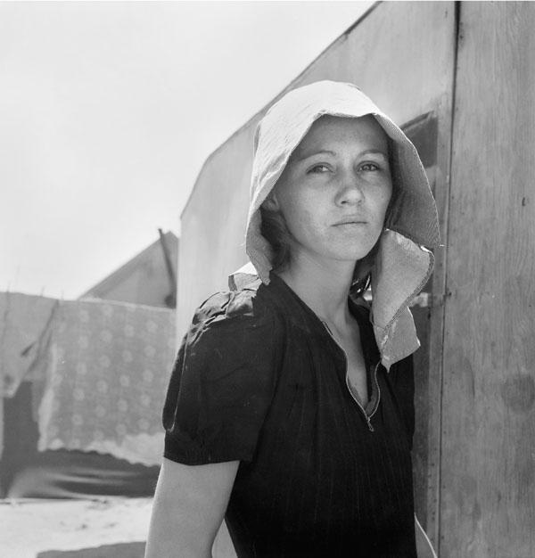 """Young migratory mother, originally from Texas. On the day before the photograph was made she and her husband traveled 35 miles each way to pick peas. They worked 5 hours each and together earned $2.25. They have two young children . . . Live in auto camp."" - at Edison in Kern County California - April 11, 1940"