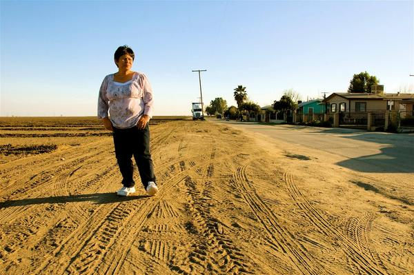 Teresa De Anda stands across her childhood home in Earlimart. This land across the street was bare for a short while after the grape fields that were there for many decades were removed to plant almond trees.