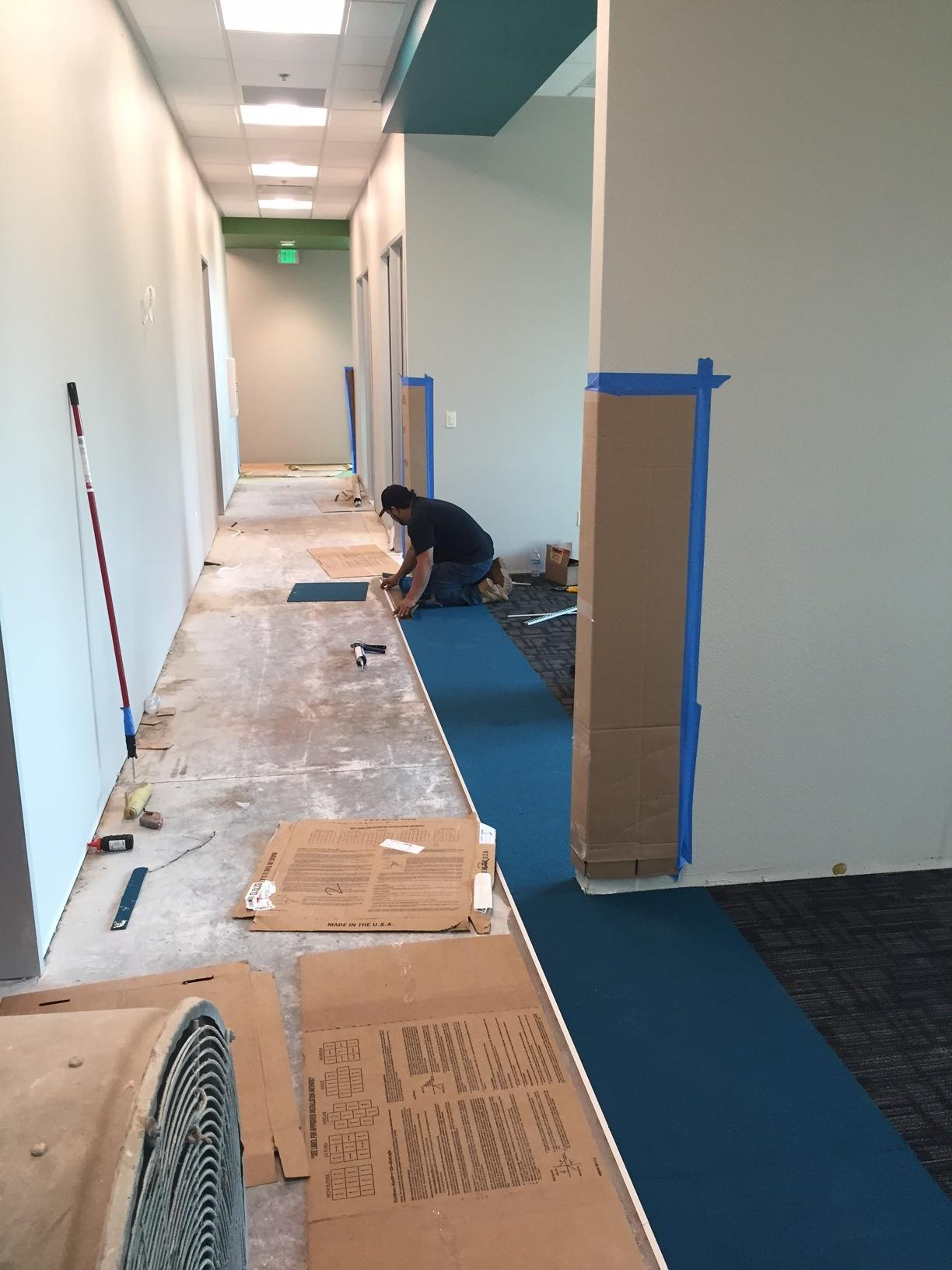 workers are busy installing carpet in the new building
