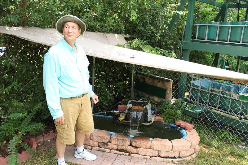 Dr. Kemp stands in front of the fish tank a part of his aquaponics model.