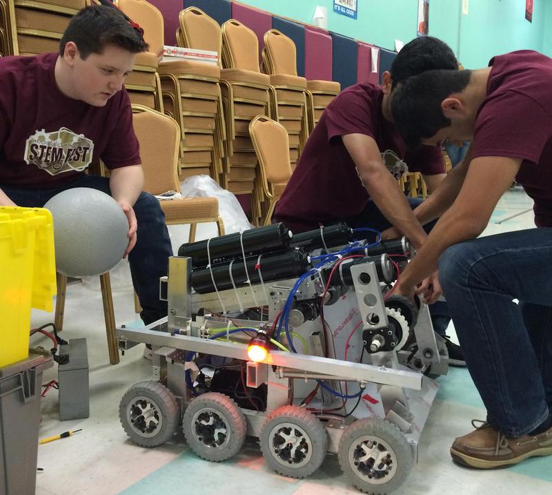 Members of the Devastators look at Impulse during Harmoney Science Academy's STEM Fest