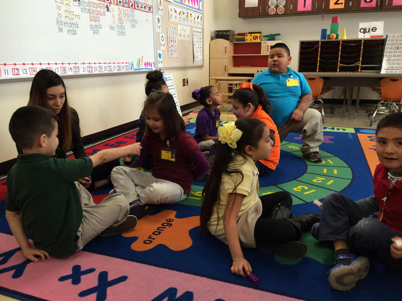 A teaching aide helps a kindergarten class. Similar ones are present in the district's pre-k programs.
