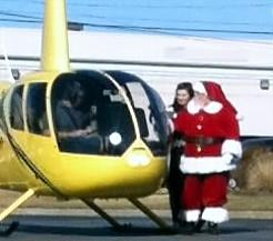 Santa steps out of a helicopter that brought him to the mall.
