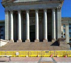 Yellow barricades block the south entrance of the crumbling capitol building.