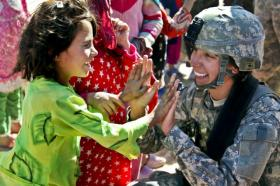 Sgt. Stephanie Tremmel, with the 86th Special Troops Battalion, 86th Infantry Brigade Combat Team, interacts with an Afghan child while visiting the village of Durani.