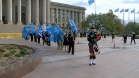 A bagpiper leads a procession of Oklahoma flags at the state capitol to mark Child Abuse Awareness Month.