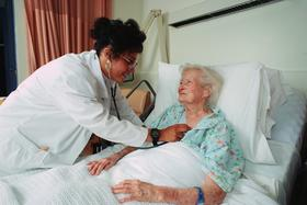 nurse checks on elderly patient