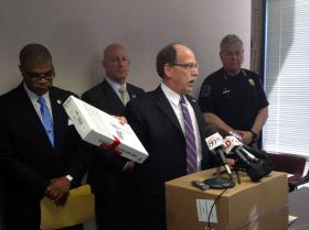 Tulsa County District Attorney Tim Harris holds up a gun seized during the course of the investigation. U.S. Attorney Danny Williams, Oklahoma Bureau of Narcotics Director Darrell Weaver and Tulsa Police Chief Chuck Jordan listen as Harris explains the trafficking problem.