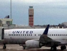 An United Airlines jet sits in the shadow of the Tulsa International Airport control tower.