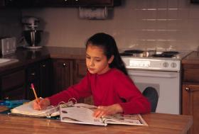 Young girl does school work at the kitchen table.