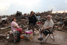 Stella and Jack Howard (left and right) with their daughter, Dawnelaina (center), sit with the remains of their Moore home.