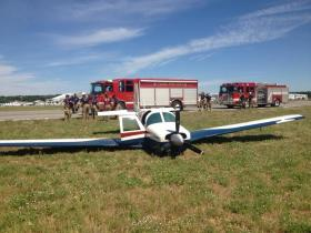 A plane slides to a stop in the grass at Tulsa's Jones Riverside Airport.