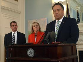 Health Care Authority CEO Nico Gomez talks with reporters as Governor Fallin and Secretary of Health and Human Services Terry Cline looks on at the state capitol.