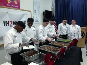 (From left) IN2WORK program graduates Gregory Byrd, Malcolm Hardridge, Paul McLaughlin and Justin Schultz plate the main as their instructors from Aramark look on Friday. The meal was the men's final exam for the food service program.