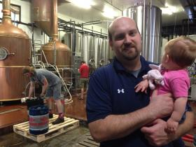 Eric Marshall holds his 1-year-old daughter while Taylor Owens (left) and Garrick Ritzky (background) tend to their duties at Marshall Brewing Company. Marshall was heavily involved in the push to get a law passed allowing the state's breweries to offer samples.