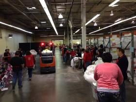 Salvation Army volunteers stand in line Thursday, waiting to fill shopping carts for families in need. The organization is distributing food and gifts to qualifying families through Saturday.
