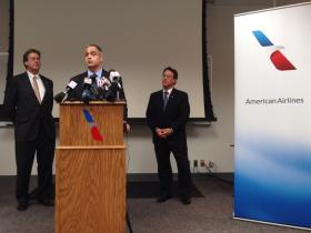 David Seymour with American Airlines Group, Inc., (center) speaks to local officials and company employees Monday morning at the Tulsa maintenance base. Mayor Dewey Bartlett (left) and Tulsa Regional Chamber President Mike Neal (right) also spoke.