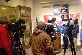 Reporters listen as Joy Hofmeister announces she will enter the race.