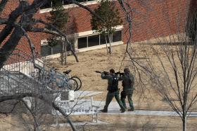 Officers will weapons drawn approach an OU Campus building.