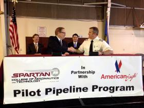Spartan College President and CEO Peter Harris (foreground, left) shakes hands Wednesday with American Eagle Director of Pilot Recruitment Nick Brice after the men signed agreements for the pilot pipeline program. Tulsa Mayor Dewey Bartlett (background, left) and Justin McLauglin, Tulsa Regional Chamber's senior vice president of economic development, were among the local officials in attendance.