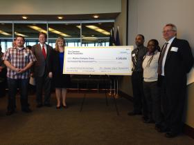 (From left) TCW graduate Brandon Fields, Tulsa Mayor Dewey Bartlett, TCW Program Director with Madison Strategies Karen Pennington, TCW graduates Richard Calhoun and Porcha Thomas, and George Kaiser Family Foundation Executive Director Ken Levit pose Wednesday with a giant check made out for the amount of The Common Bond Foundation's donation to the workforce development program.