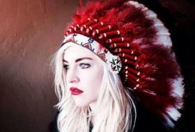 Christina Fallin wearing a headdress in a publicity photo for her band.