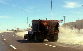 A snow plow/salt truck treats I-244 near Memorial exit in Tulsa.