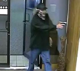 The bandit enters the bank with his gun.