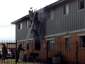 A Tulsa firefighter opens a hole in the roof of one of the Saint Thomas Square apartments that caught fire Wednesday morning.
