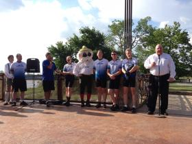 Linde Processing Plants CEO Steve Bertone (right) speaks at the announcement of the company's title sponsorship of Tulsa's Oktoberfest celebration. He was joined by members of the company cycling team.