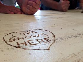 Supporters of the Tulsa's Table community café carve their initials into a table that will be used by the restaurant.