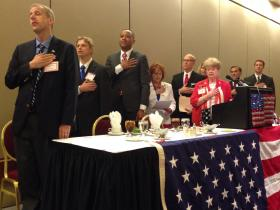 Kevin Crow (left), Andy Craig, T.W. Shannon, Brenda Tiemann, Jerry Buchanan, Cindy Lankford, Randy Brogdon, Eric McCray and Connie Ullman (in red) recite the Pledge of Allegiance Tuesday before the Republican Women of Tulsa County's candidate forum.