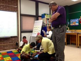 Tulsa Public Schools Superintendent Keith Ballard (right) and Chief Academic Officer Tracy Bayles look in on students Wednesday in Bridgette Mangrum's summer reading academy class.