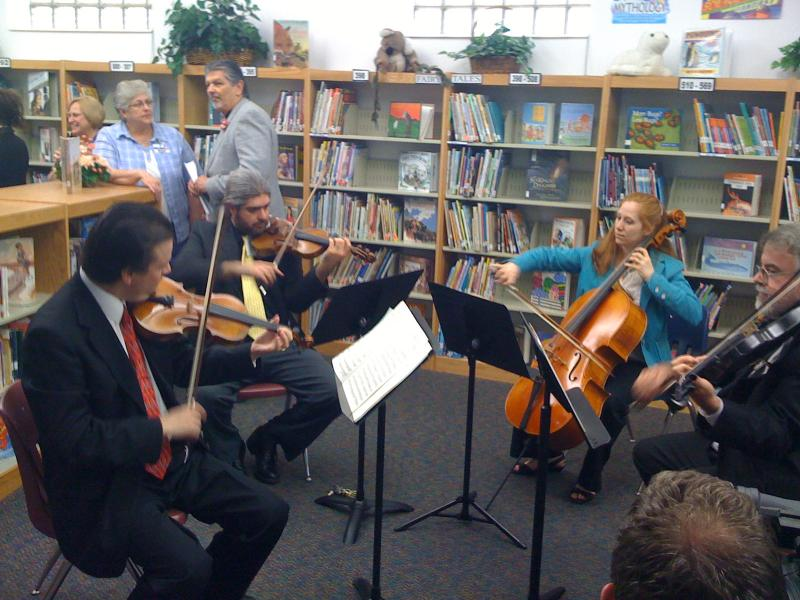 The Signature Symphony's string quartet performs at the Eugene Fields Elementary School in West Tulsa as the Mentoring to Music program is announced.