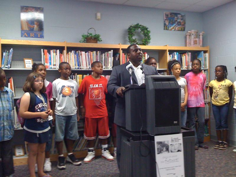 Alcott Elementary Principal Julian Wilson, surrounded by school children, discusses the grant for the Tulsa Mentoring program.