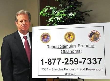 U.S. Attorney David O'Meilia next to the fraud hotline number