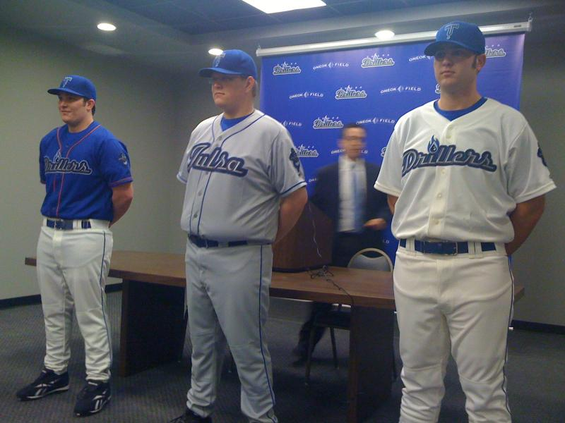 General Manager Mike Melega (in background) shows off new Tulsa Driller uniforms.