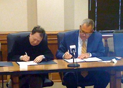 TU President Steadman Upham signs a cultural exchange agreement with China's Daming Palace Academy.
