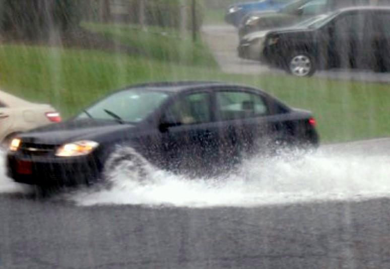 A car runs through high water in south Tulsa.